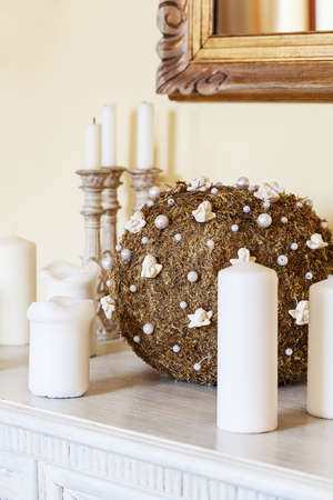 Mediterranean interior - a golden ornaments and white candles Stock Photo - 21363352