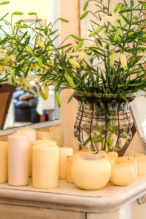 mediterranean interior: Mediterranean interior - flowers in a vase and cream candles