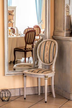 Mediterranean inter - a stripped chair by a framed mirror Stock Photo - 21363371