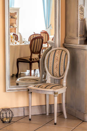 Mediterranean interior - a stripped chair by a framed mirror Stock Photo - 21363371