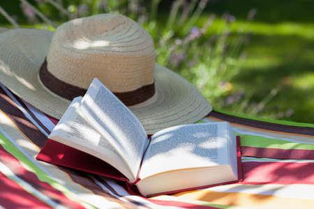 tembellik: Bir kitap ve bir hamak üzerinde yatan bir şapka Stok Fotoğraf