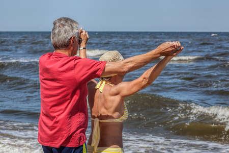 Happy senior couple holding hands at seaside photo
