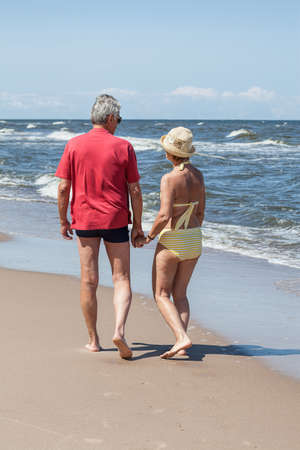 Happy old couple walking on the beach photo