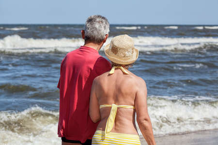 Curious seniors looking at blue beautiful sea photo