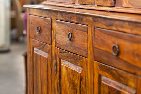 A closeup od a dark brown wooden cabinet with drawers Stock Photo