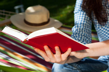 An opened red book in womans hands Stock Photo