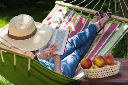 Una mujer se relaja en una hamaca con una novela