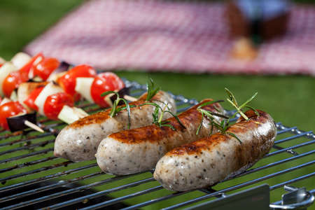 coal fire: White sausages grilling during a summer barbecue