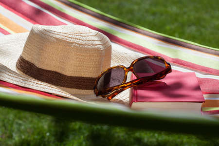 Straw hat, sunglasses and book on a hammock photo