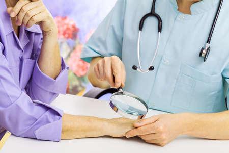 dermatologo: Dermatologo guardando la mano di donna attraverso una lente di ingrandimento Archivio Fotografico