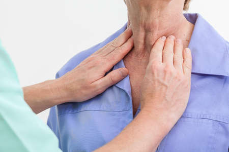 a diagnosis: Problems with thyroid, nurse examining a patient Stock Photo