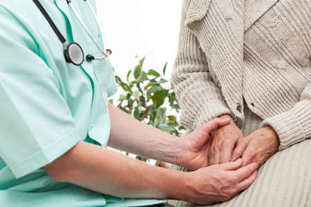 Doctor keeping an elderly patients hands photo