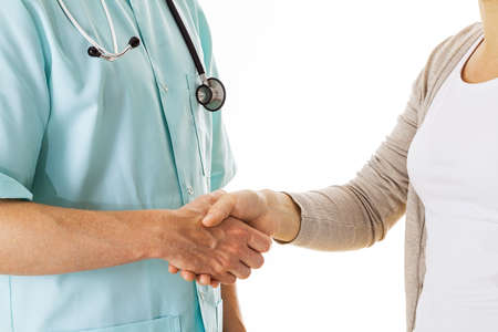 grateful: Doctor shaking hand with a patient, isolated background Stock Photo