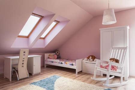 Städtische Wohnung - niedliche rosa Mädchen im Zimmer auf dem Dachboden