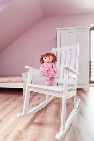 Urban apartment - pink doll on a white rocking chair Stock Photo - 21822144