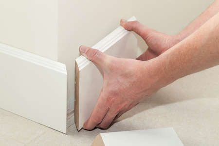 Man putting new skirting board in house Stock Photo