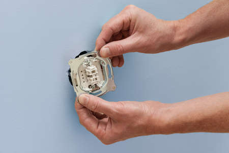 Do it yourself, mans hands installing a new power socket Stock Photo - 21822478