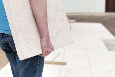 Closeup of repairman carrying concrete slab Stock Photo - 21822485