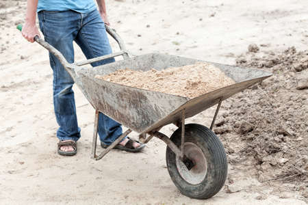 Man with barrow full of ground, work in garden photo