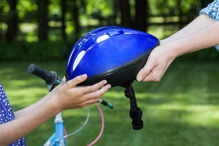 blue helmet: Close up of bicycle helmet held by two people