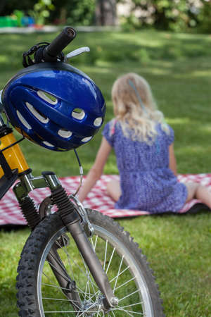 Little blond girl sitting on a blanket in a park after biking photo