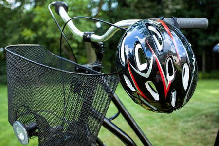 bicycle helmet: Basket and helmet of a bike in the park Stock Photo