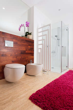 Pink orchid and cozy red carpet in bathroom photo