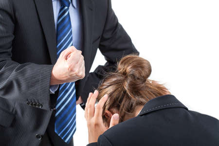 violence in the workplace: Boss is clamping his fist above frightened worker