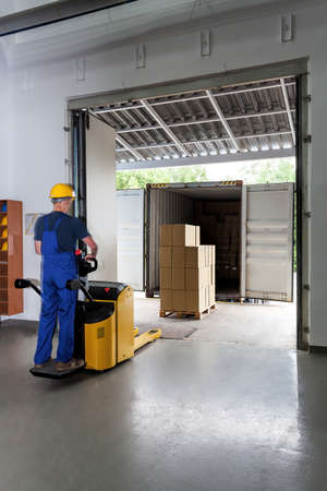 forklift: Delivering packages in a spacious warehouse By a worker