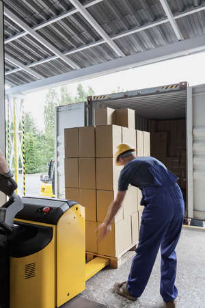 deliver: Unloading of articles in the warehouse by a worker Stock Photo