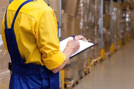 Close-up van een werknemer met een lijst controleren van voorraad staat Stockfoto