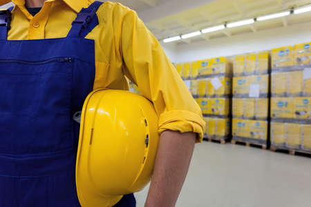 Closeup of a blue collar worker holding hard hat photo