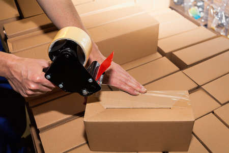 packing boxes: Worker using adhesive tape to close the boxes