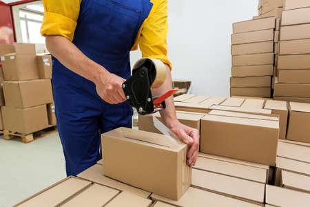 Ouvrier d'usine avec distributeur de fusil de ruban d'emballage finir une livraison
