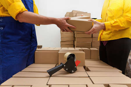 packing: Factory workers packaging a products into a boxes