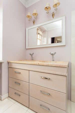 chest of drawers: Vintage mansion - a stone washibasin on a chest of drawers, a mirror and lamps Stock Photo