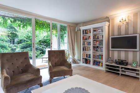 ビンテージ マンション - 本棚と茶色の肘掛け椅子での読書コーナー 写真素材