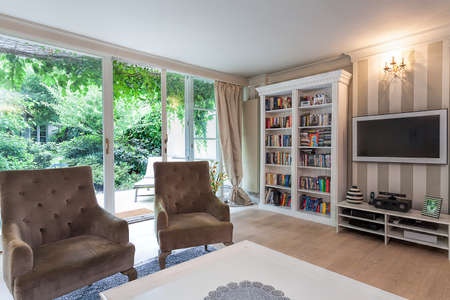 Vintage mansion - a reading corner with a bookshelf and brown armchairs