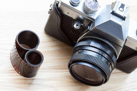 A stylish reflex analogue camera and a roll of film photo