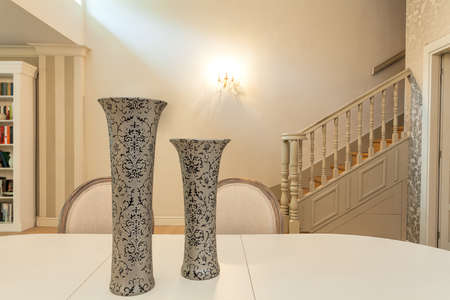 Vintage mansion - a closeupof two patterned vases on a cream table photo