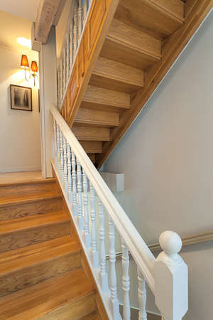 Vintage mansion - brown wooden stairs with a white barrier