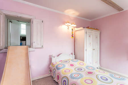 Vintage mansion - a pink room with a slide and a bed photo