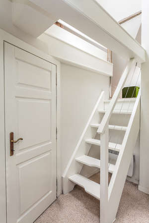attic: Vintage mansion - white wooden attic stairs and a door