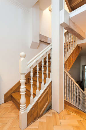 Vintage mansion - a landing of a wooden staircase with white details photo