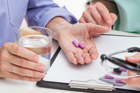 pacientes: Un primer plano de pastillas y un vaso de agua