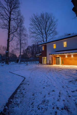 Driveway to modern house in winter scenery photo
