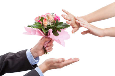apologise: Man giving flowers to his wife after argument, isolated background Stock Photo