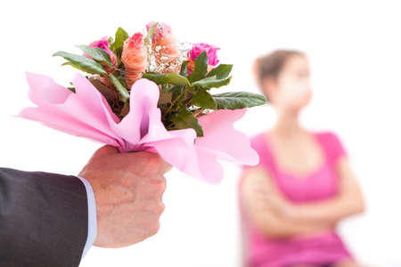 apologise: Man with flowers trying to offer an apology to his wife Stock Photo