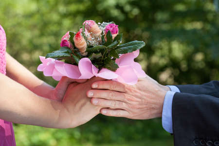 Man giving a bouquet of flowers to his lady photo