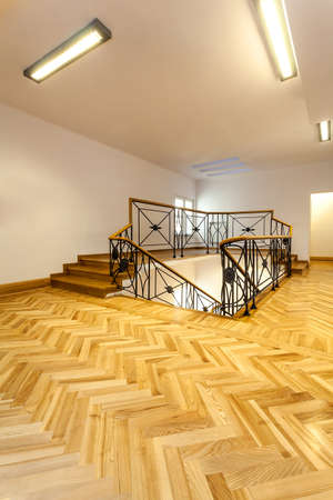 Bright hall with wooden parquet and elegant staircase photo